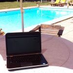Arbeiten mit Laptop am Pool